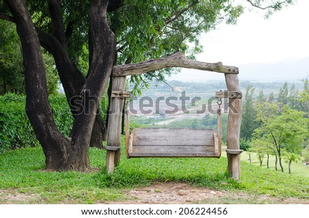 Old wooden bench swing under tree in the garden. - stock photo