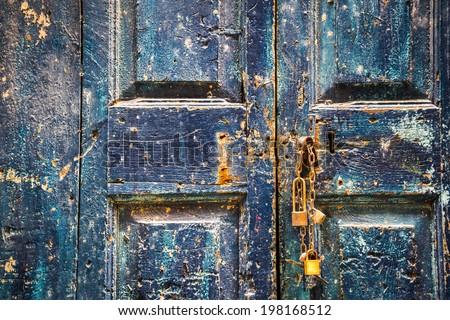 Old wooden blue door with padlocks - stock photo