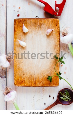 Old wooden board on white background with herbs, spices and cooking utensils. Central space for copy / text. - stock photo