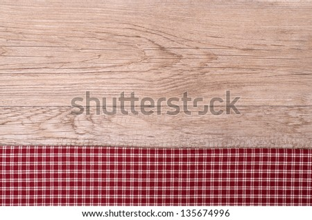 Old wooden board with checkered cloth as background - stock photo