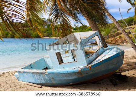 Old wooden boat at tropical beach with palm trees, white sand, turquoise ocean water and blue sky at Antigua Island in Caribbean - stock photo