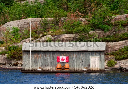 Old wooden boathouse with two Muskoka chairs and Canadian flag - stock photo