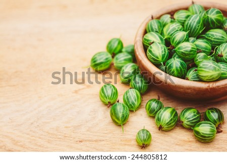 Old Wooden Bowl Filled Succulent Fresh Ripe Green Organic Berries Gooseberry Gooseberries - stock photo