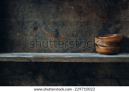 Old wooden bowls, placed on a wooden shelf - stock photo