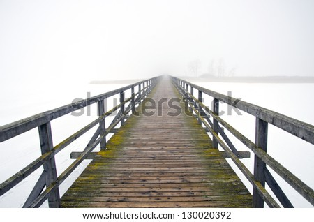 old wooden bridge in winter and mystery morning fog