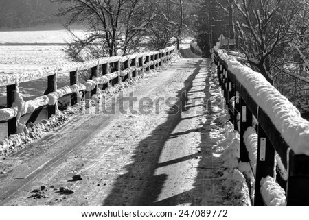 Old wooden bridge in winter, covered with snow. - stock photo