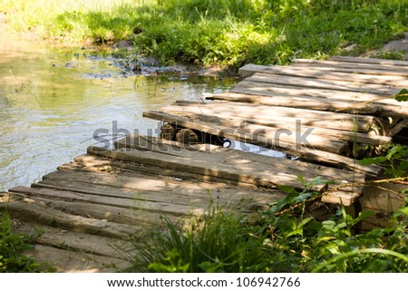old wooden bridge on the river - stock photo