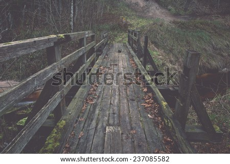 old wooden bridge over small river. autumn. - retro, vintage style look - stock photo