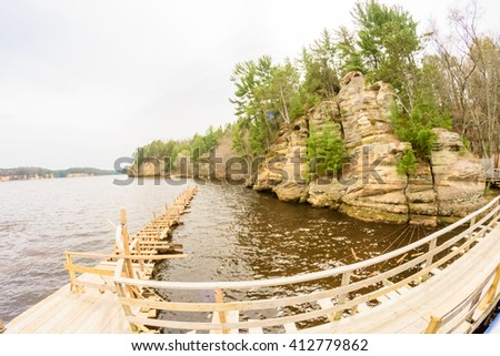 Old wooden bridge through the river with green trees - stock photo
