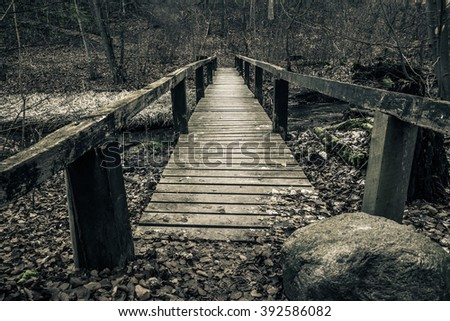 Old wooden bridge with planks in a forest