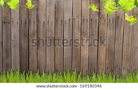 Old wooden brown fence. Grass against wooden background. Place for your text.