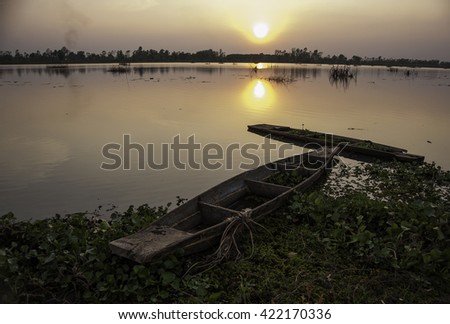 Old wooden canoe fishing boat showing vegetation growth within boat, filled with water after heavy rain storm.