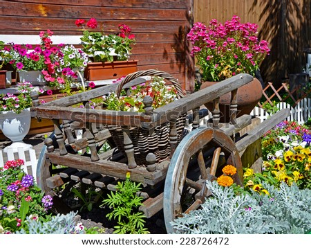 Old wooden cart, baskets and pots full of flowers