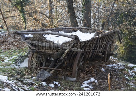 old wooden cart in the snow - stock photo