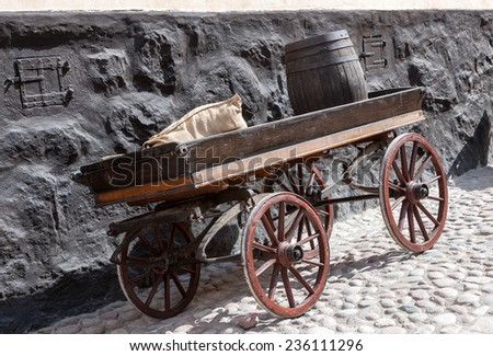 old wooden cart  with a bag and a barrel on background of old brick wall - stock photo