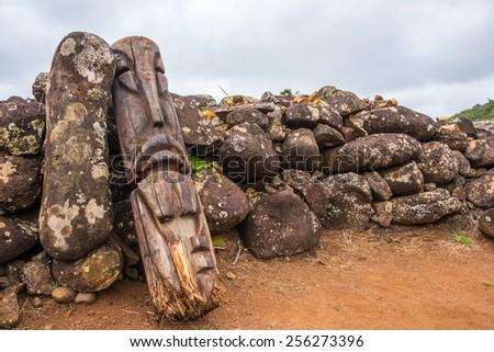 Old wooden carved Tiki god, broken up against volcanic stones on sacred grounds - stock photo