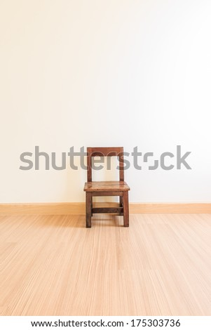 Old wooden chair on laminate flooring in the room - stock photo