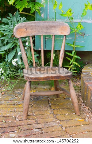 Old wooden chair propping open a door in a garden - stock photo