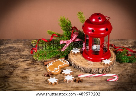 Old wooden christmas background with gingerbread cookies, lantern and fir branch, empty space for text