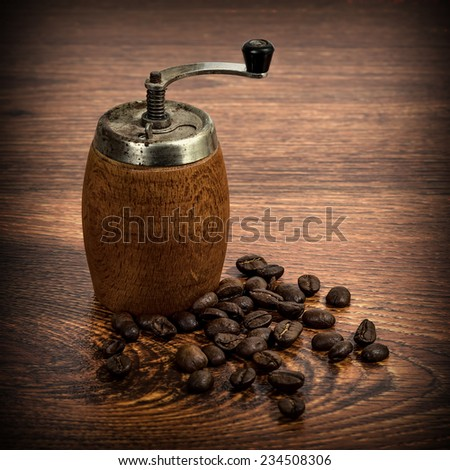old wooden coffee grinder with grains of coffee - stock photo