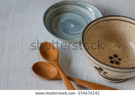 old wooden cooking spoon on vintage white table with china cup - stock photo