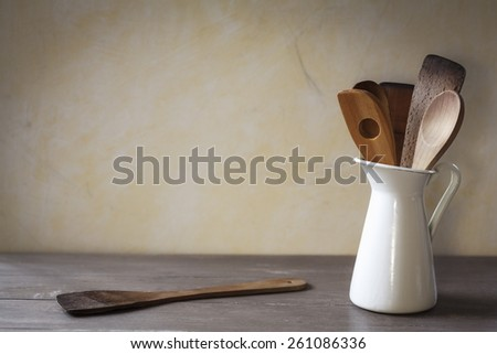 Old wooden cooking spoons in white jug - stock photo