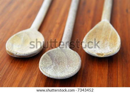 Old wooden cooking spoons on a cutting board in a kitchen