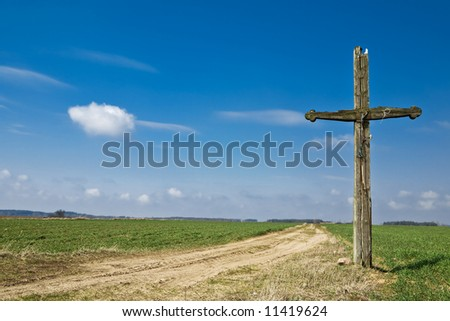 Old wooden cross at country road. Green grass and blue sky. - stock photo