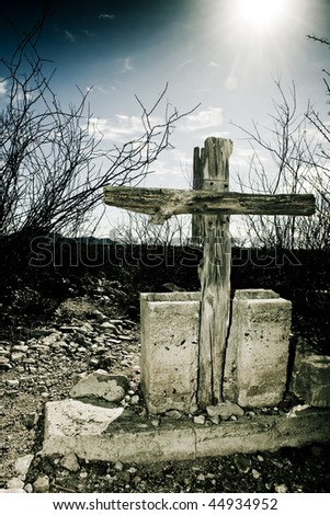 Old wooden cross with cement base from Arizona ghost town graveyard with a clouded sky - stock photo