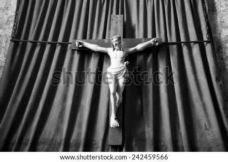 Old wooden crucifix of Jesus Christ isolated on drapery background in medieval church. Aged photo. Black and white. - stock photo