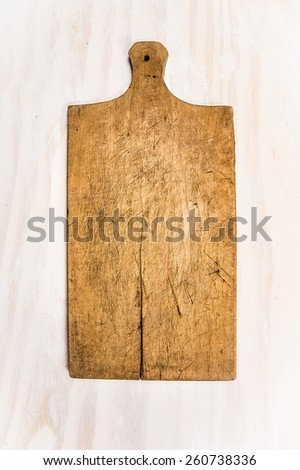 Old wooden cutting board on white wooden background - stock photo