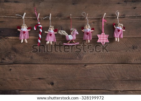 Old wooden dark brown christmas background with handmade red white checked decoration objects like angel, stars and hearts. - stock photo