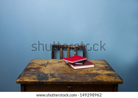 Old wooden desk and chair with books and a pen - stock photo