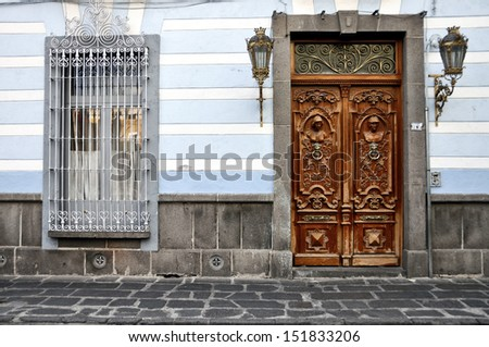 Old wooden Door and Window with bars in Puebla, Mexico - stock photo