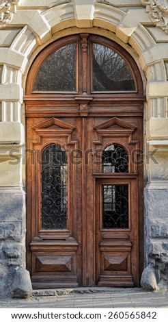 Old wooden door close-up on a background of a wall - stock photo