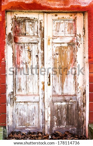 Old wooden door covered with cracked, worn paint - stock photo
