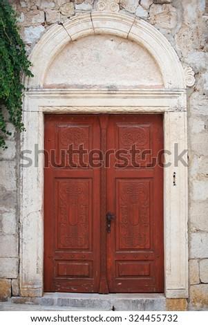 Old wooden door in city of Rab, Croatia - stock photo
