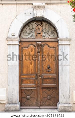 Old wooden door in Lourdes, Hautes Pyrenees, France - stock photo