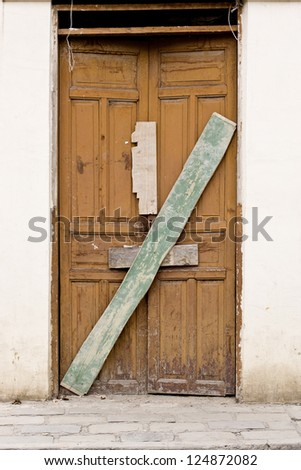 Old wooden Door in Old wall colonial Latin America - stock photo