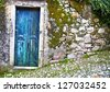 Old wooden door in stone wall. Portugal. Sintra - stock photo