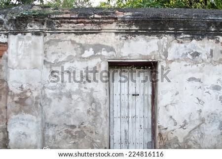 Old wooden door is locked on old plaster walls. - stock photo