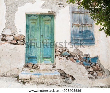 Old wooden door of a shabby demaged house facade or front in blue, green and turquoise. - stock photo
