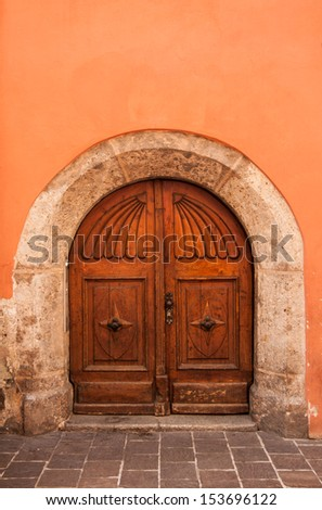 old wooden door orange wall background with stoned frame - stock photo
