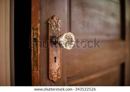 Old wooden door with a crystal door knob.  - stock photo