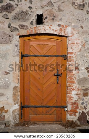 Old wooden door with iron bands and padlocks - stock photo