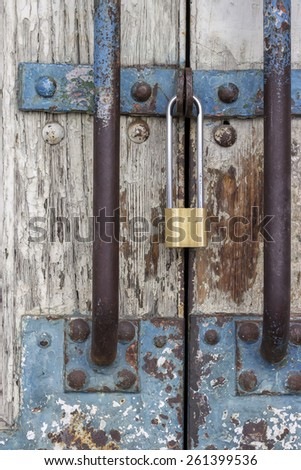 Old wooden door with locked padlock, entrance to the warehouse - stock photo