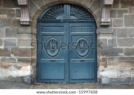 Old wooden door with metal and wooden ornaments - stock photo