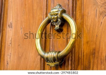 Old wooden door with metal knocker - stock photo