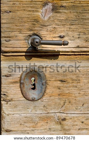 Old wooden door with rusty metal handle and key lock - stock photo