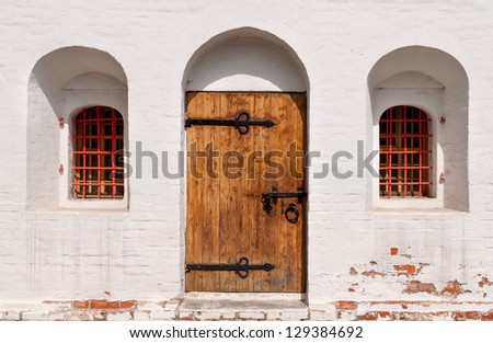 old wooden door with white wall - stock photo